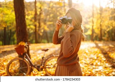 Hermosa joven toma fotos con una cámara retro en el bosque de otoño. Niña sonriente disfrutando del clima otoñal. Descanso, relajación, concepto de estilo de vida.