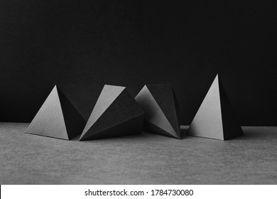 Platonic solids figures geometry. Abstract geometrical figures still life composition. Three-dimensional prism pyramid objects on black gray background