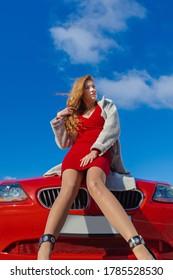Schöne blonde Frau in einem roten Kleid, das in einem roten Auto in der Stadt an einem sonnigen Tag aufwirft