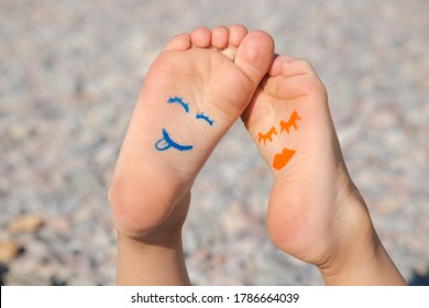 Oranje vrouwelijke en blauwe mannelijke gezichten worden getekend op de blote voeten van een kind dat op het strand ligt. Zonnige dag, vrolijke positieve sfeer, gelukkige jeugd, leven met vreugde. Zomer strandvakantie