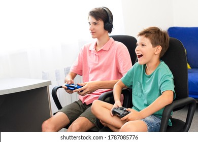 Teenager plays a computer game with headphones and a joystick, game console.