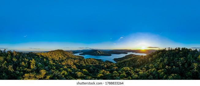 Natürliches See-Luftpanorama mit Gebirgslandschaft und Waldhintergrundreflexion von Wolken auf plätscherndem Wasser. Szenische entspannende Landschaft an einem klaren Sommertag 4K HD High Definition
