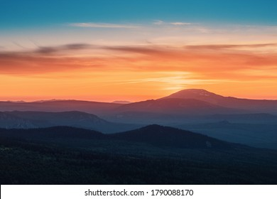 A rocky mountain range covered in the wild woods illuminated by the golden light of the setting sun. A natural Park reserve or hunting grounds. Recreational outdoor tourism