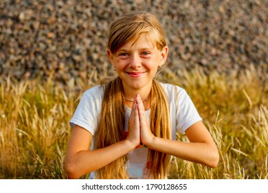 Happy little girl folded her hands in palm hand in front of chest, sincerely believes fulfillment to dreams, makes wish. prayer concept for faith, spirituality and religion. Practicing meditate yoga