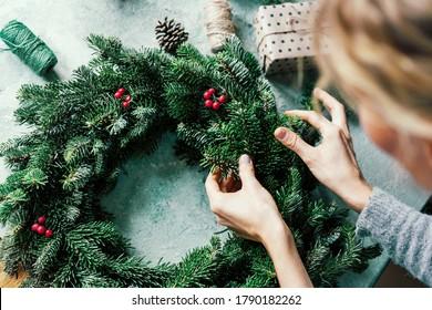 Frau macht einen Tannenkranz für den Advent. Heiligabend und Dekorieren. Neujahr Feierlichkeiten.