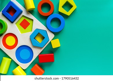 Wooden toys, shape sorter board on green background. Back to school.  Close up. Top view, copy space. Educational, logical mathematical  games for kindergarten, preschool kids