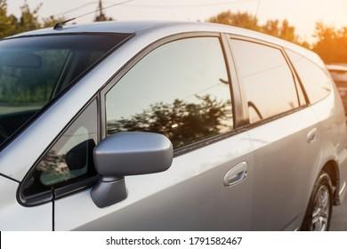 Vorderansicht eines japanischen Autos Honda in der Karosserie eines Schrägheckmodells an der Seite eines silbernen Kombis auf einem Parkplatz mit grünen Bäumen, nachdem es zum Verkauf gewaschen wurde.