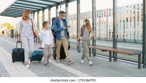 バス停や駅を歩いて、スーツケースを車輪に乗せて話している2人のかわいい小さな子供を持つ白人の幸せな家族。旅行中の医療用マスクに幼い娘と息子がいる親。