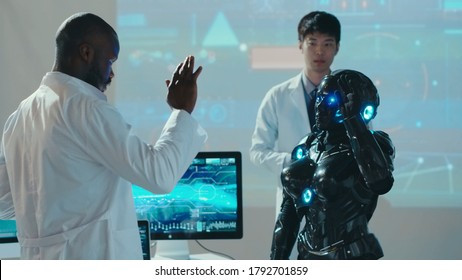 Interracial research team testing the new futuristic automated android in lab. Cybernetic black robot waving hand repeating scientist moves. Artificial intelligence.
