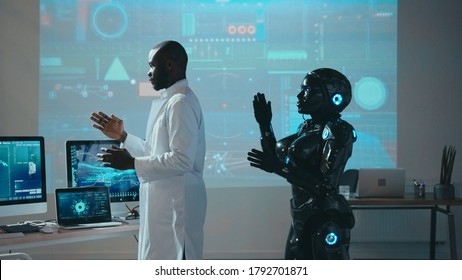 Black automated robot repeating moves after male scientist in futuristic high tech laboratory. Innovations. Robotic industry. Artificial intelligence. Cooperation.