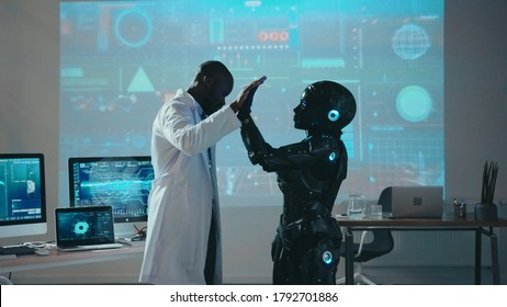 Black scientific engineer giving high-five to android automated robot on futuristic presentation in the laboratory. Artificial intelligence. Robotic science. Technologies.