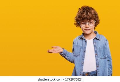 Nettes Kind im Jeanshemd und in den Gläsern, die Kamera betrachten und auf Leerraum lokalisiert auf gelbem Hintergrund zeigen