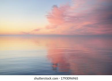 Ostsee nach dem Regen bei Sonnenuntergang. Dramatischer Himmel mit leuchtend rosa Wolken, Symmetriereflexionen im Wasser. Abstraktes natürliches Muster, Textur, Hintergrund, Konzeptkunst
