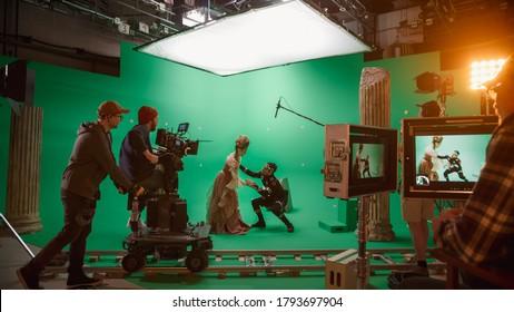 Op Big Film Studio Professionele crew schieten Geschiedenis Kostuum Drama Film. Op de set: regisseren van greenscreen-scène met mooie dame in renaissancekostuum ontmoet acteur die monster speelt