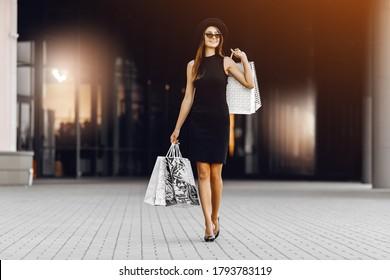 自信を持って、幸せで、魅力的な若い女性が黒いドレスと帽子をかぶって、暗い眼鏡をかけ、ショッピングセンターの前で買い物袋を持っています。ブラックフライデー、ショッピング