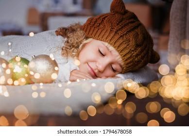 Mädchen in Strickmütze in der Nähe von Weihnachtsbaum macht einen Wunsch für neues Jahr. Glückliches kleines Mädchen aufgeregt an Heiligabend. Hoffnungskonzept Warten auf Weihnachtsmann. Hoffnungsvolles Kind. Silvester. Träume werden wahr.