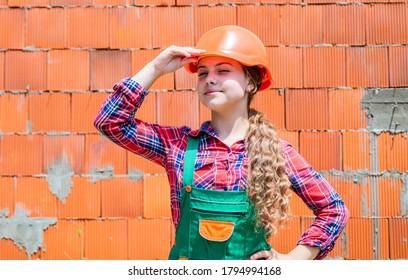 girl in helmet is construction worker. foreman teen child. kid work in the helmet. little girl in a helmet. girl making repairs. teen dressed in hard hat. concept of childhood development.
