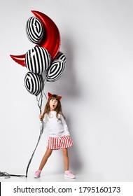 meisje in een witte trui en korte broek, haarring met rode duivelshoorns. Ze houdt een bos ballonnen in haar rechterhand en haar linkerhand in haar zak, uitdrukking van verbazing, naar rechts leunend