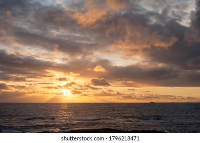 Puesta de sol de paisaje marino, océano oscuro, con sol oculto por nubes amarillas, mezcla de otros colores. Rayos de sol de color amarillo brillante que llegan al océano, nubes amarillas, naranjas, grises y blancas.