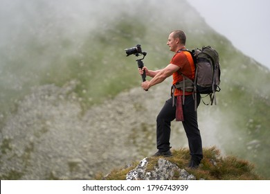 Professional videographer shooting with a gimbal high in the mountains