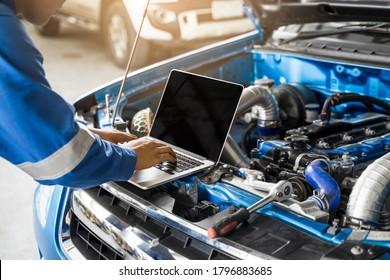 Mechanischer asiatischer Mann schließen oben unter Verwendung des Laptop-Computers, der Tuning-Reparatur repariert, die Auto-Motor-Fahrzeugteile des Werkzeugmotors unter Verwendung der Werkzeugausrüstung im Werkstattgaragen-Unterstützungsdienst in der Gesamtarbeitsuniform repariert