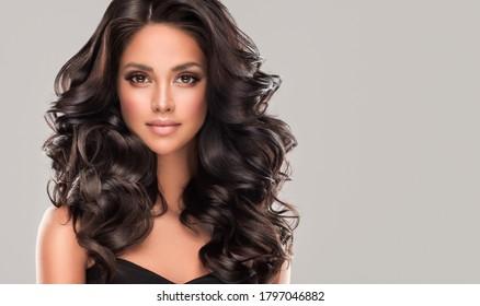 長くて光沢のある波状の黒い髪の美しさのブルネットの女の子。巻き毛の美しい女性モデル。