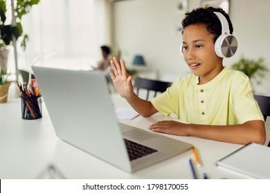 笑顔の黒人の少年がノートパソコンでビデオ通話をし、自宅でeラーニングをしながら手を振っています。