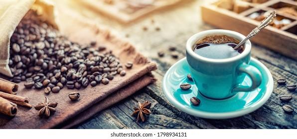 Eine türkisfarbene Tasse aromatischen schwarzen Kaffees und Kaffeebohnen auf dem Tisch. Morgenkaffee Espresso zum Frühstück in einer schönen türkisfarbenen Tasse.