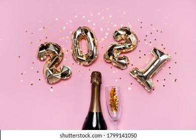 2021年の金箔の風船の番号、シャンパン、星の紙吹雪、リボン、ボケ味。トップ水平ビューコピースペース新年と休日のコンセプト。