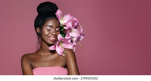 ピンクのアートと若いアフリカ系アメリカ人モデルのファッションの肖像画は、ピンクの背景にユリの花でポーズを構成します。