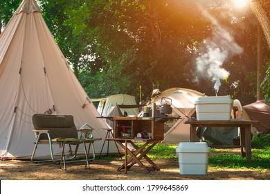自然公園のキャンプ場に野外テントグループが設置された屋外キッチン設備と木製テーブル