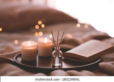 Palitos de bambú en botella con velas perfumadas y libro abierto en bandeja de madera en primer plano de la cama. Aroma casero.
