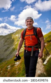 Professional nature photographer hiking with a backpack in the high mountains