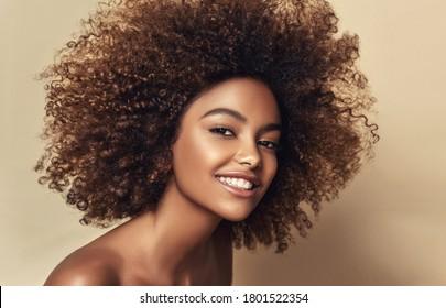 ベージュの背景にきれいな健康な肌を持つアフリカ系アメリカ人女性の美しさの肖像画。美しいアフロの女の子の笑顔。巻き毛の黒い髪。