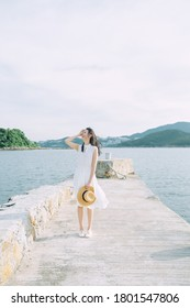 Asian Chinese young female girl in white one piece dress with hat. Blue sky summer outdoor airy breeze