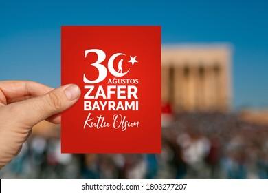 Männliche Hand, die ein rotes Papier mit Grußnachricht auf Türkisch hält. Glücklicher 30. August, Tag des Sieges in Englisch. 30. August, Zafer Bayrami ist der Siegertag der Türkei.