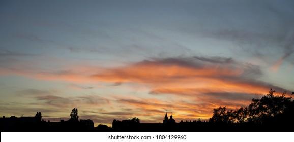 Atardecer atmosférico otoñal en fantásticos tonos de naranja y rosa con el telón de fondo de un horizonte de la ciudad con una iglesia