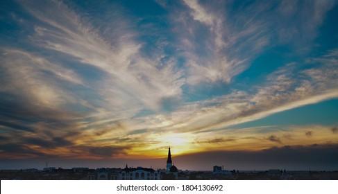 Fantástico atardecer amarillo y blanco otoñal con panorama de la ciudad e iglesia