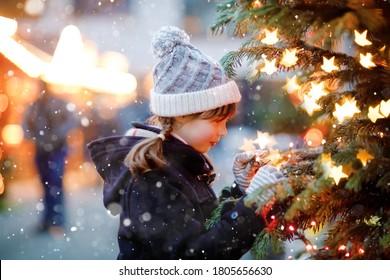 強い降雪の間に伝統的なクリスマスマーケットで楽しんでいる小さなかわいい子供の女の子。ドイツの伝統的な家族市場を楽しんでいる幸せな子供。照らされたクリスマスツリーのそばに立っている女子高生。