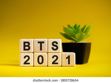 BTS - business financial concept on a yellow background. Wooden cubes and flower in a pot.