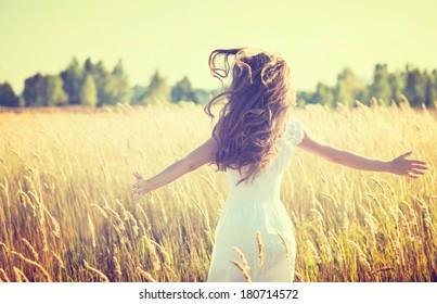 自然を楽しむアウトドアビューティーガール。春のフィールド、太陽の光で実行されている白いドレスを着た美しい10代のモデルの女の子。
