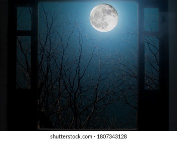 View from blurred old wooden window of spooky house looking at full moon on the dark night