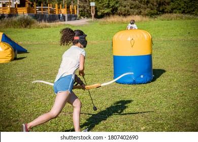 Teenager-Mädchen, das mit Pfeil und Bogen während eines Spiels des Bogenschießens läuft