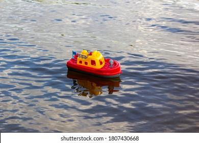 川に浮かぶおもちゃの船。鮮やかな赤と黄色のプラスチック製の船。おもちゃのハンドル。子供の水のおもちゃ。子供の海の旅の夢。自然の中で子供たちとのゲーム。