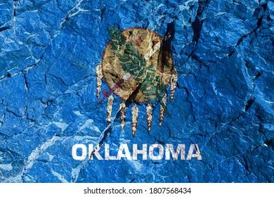 空色の背景に米国オクラホマ州の国旗があり、中央には7つのワシの羽が付いた水牛の皮で作られた伝統的なオセージの盾があります。登山中の登山者の岩の落書き