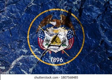 山の壁に描かれたタロンに矢印が付いた白頭ワシの金色の境界線に囲まれた、中央にシールが付いた青い背景の米国ユタ州の国旗。