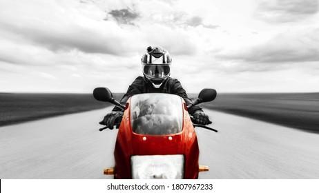 Een man rijdt snel op weg naar de camera op een rode motorfiets. Zwart-wit foto