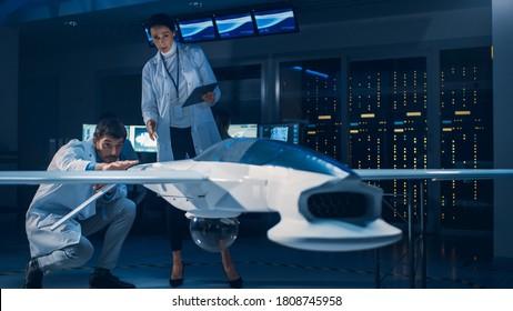 Reunión de ingenieros aeroespaciales que trabajan en prototipos de vehículos aéreos no tripulados / drones. Científicos de la aviación en batas blancas hablando. Aviones comerciales de vigilancia aérea en laboratorio industrial