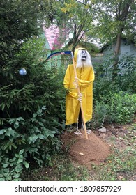 Scarecrow of death with a scythe in a yellow cloak