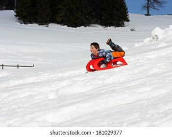 jonge jongen komt naar beneden met de rode slee in de bergen op de witte sneeuw